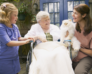 A young girl and a woman holding a cat talking to a white-haired woman with oxygen tube in nose.