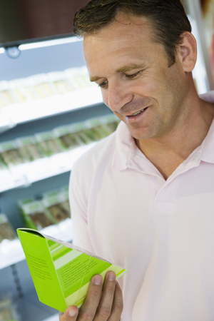 Man in grocery store reading nutrition label on package.