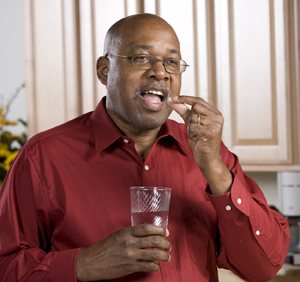Man putting pill in his mouth while holding glass of water.