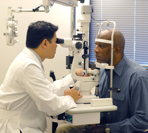 Healthcare provider examining man's eyes with slit lamp.