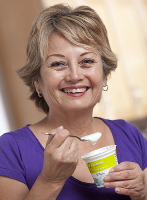 Woman eating yogurt from small container.