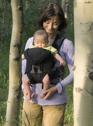 Woman walking outdoors with baby in front carrier.
