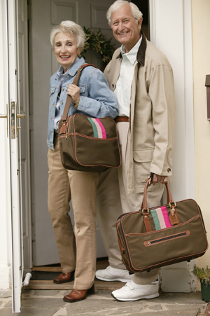Older man and woman leaving house with overnight bags.