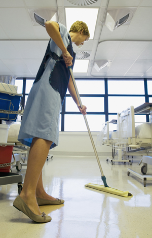Health care provider cleaning hospital room floor.