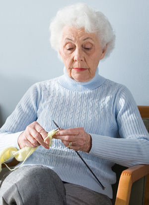 Older woman sitting in chair, knitting.