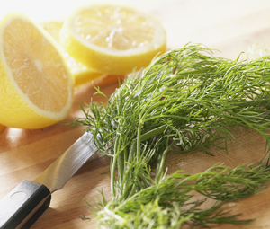 Lemons and fresh herbs on cutting board with knife.