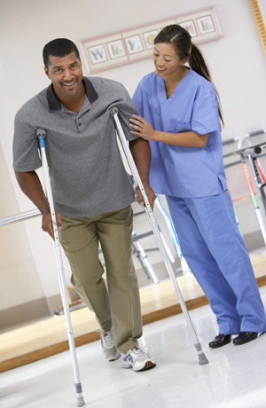 Healthcare provider helping man walk with crutches.