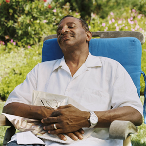 Man in chair outside, relaxing with eyes closed.