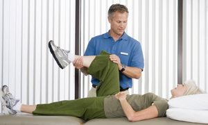 Woman lying on table. Physical therapist is bending woman's leg.