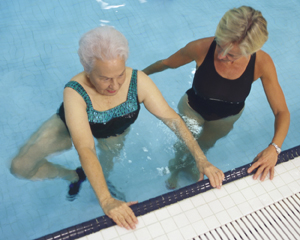 Two women in pool doing water exercises.