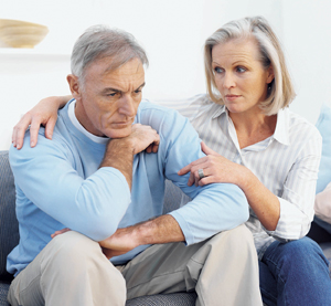 Man and woman sitting on couch, woman has arm around man looking at him with concern. Man looks very serious.