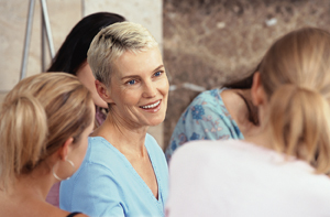 Mature woman talking to group of young women.