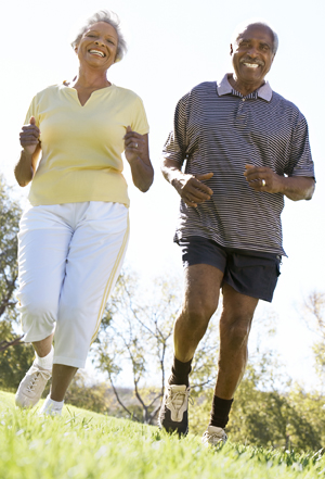 Mature African-American couple jogging outdoors.