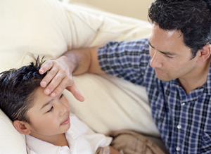 Boy sick in bed, father gently touching boy's forehead.