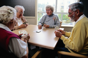Four seniors playing cards at table.