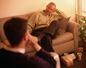 Man sitting on couch talking with therapist.
