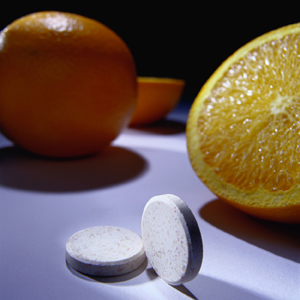 Vitamin C tablets and oranges on table.