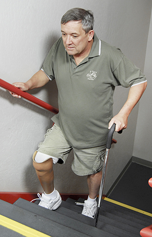Man with prosthetic leg walking upstairs with cane.