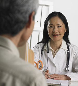 Female doctor talking to mature male patient.