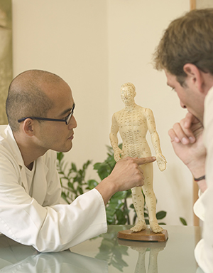 Male acupuncturist by patient, pointing at acupuncture point on model.