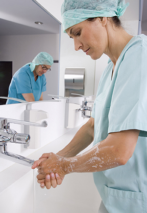 Healthcare provider washing hands in hospital room.