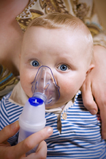Woman holding baby in lap, holding nebulizer mask over his nose and mouth.