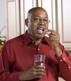 Man taking pill with glass of water.