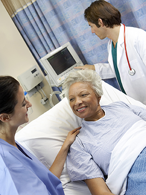 Woman in hospital listening to doctor while another healthcare provider checks monitor.