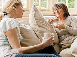 Women sitting on couch, talking, with coffee.