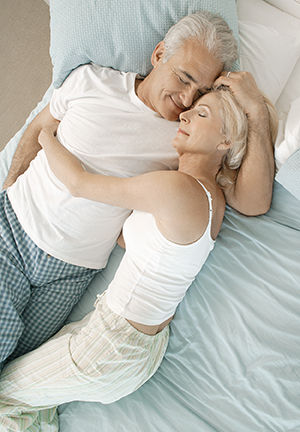 Older man and woman cuddling in bed.