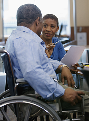 Woman assisting man in wheelchair to research and make list.