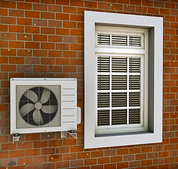 Photo of an air conditioning heat pump mounted on an outside wall next to a closed window