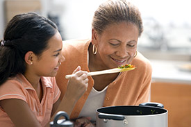Woman leaning over a stove, smelling food in a spoon. The spoon is held by a young girl.