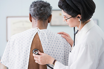 Doctor pressing stethoscope to man's back and listening