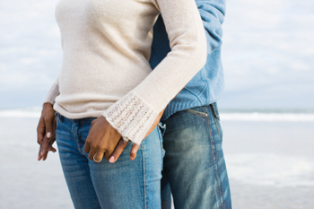 Close-up view of couple holding hands on the beach