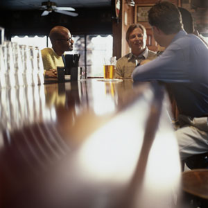Four men sitting at a bar in a pub.