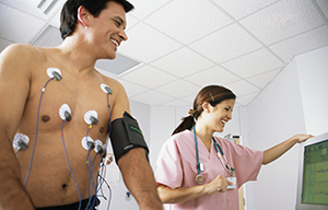 Man with wires attached to chest walking on treadmill. Health care provider is taking Man with leads attached to chest walking on treadmill. Health care provider watching monitor.