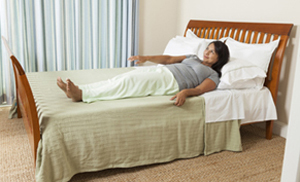 Woman rolling on to her side in bed.