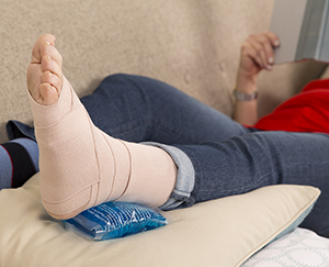 Closeup of elevated foot with bandage and ice pack.