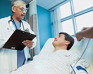 Man in hospital bed talking to healthcare provider.