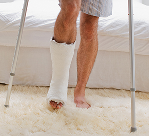 Man with cast on foot and lower leg walking with crutches.