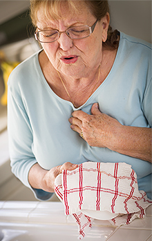 A senior woman in the kitchen holding her chest in pain.