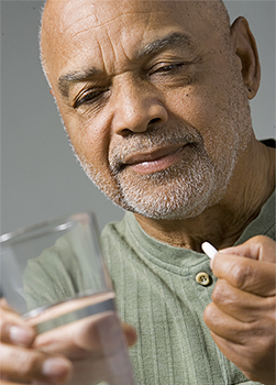 Senior man about to take a pill with a glass of water.