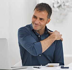 Man working at a desk, on laptop computer, holding shoulder in pain.