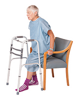 Woman lowering herself into chair - keeping operated leg slightly out in front.