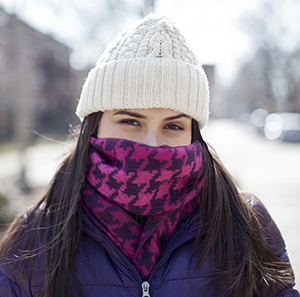 Woman wearing winter scarf over nose and mouth.