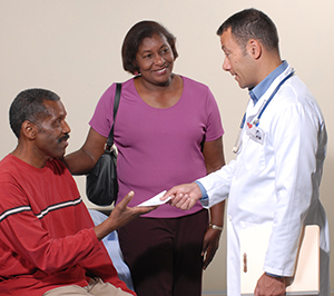 Doctor talking to patient and caregiver.