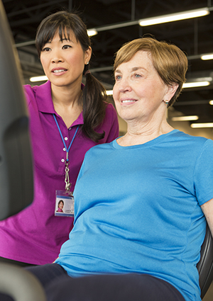 Physical therapist helping woman on exercise bike.