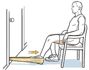 Man sitting on chair with heel in resistance band, doing hamstring curl exercise.