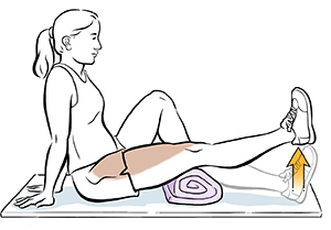 Seated woman doing straight leg raise with towel under knee.